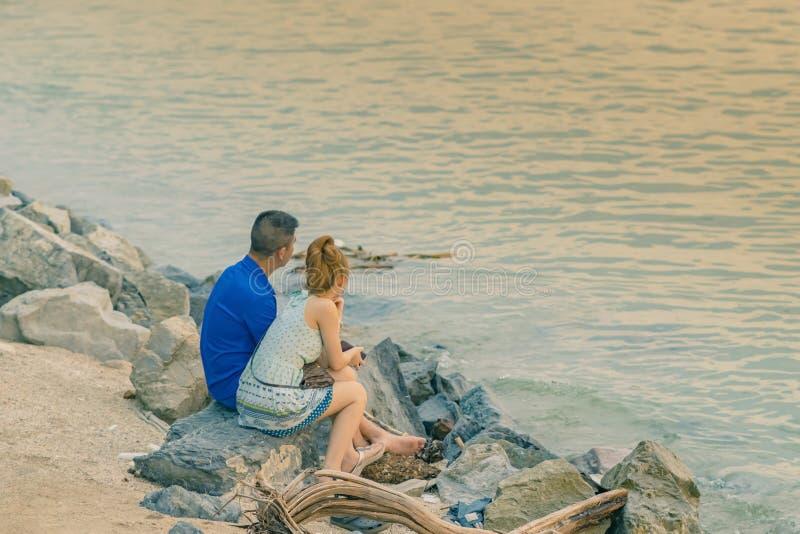 年轻夫妇后面看法一起坐在享受日落的海洋前面的石头 免版税库存照片