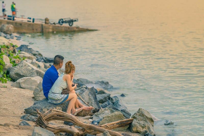 年轻夫妇后面看法一起坐在享受日落的海洋前面的石头 库存图片