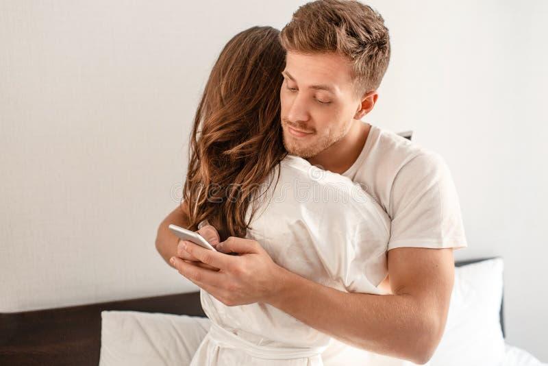 年轻夫妇在卧室 微笑的不忠实的人是欺诈和发短信给电话的恋人,当拥抱他的时 免版税库存图片