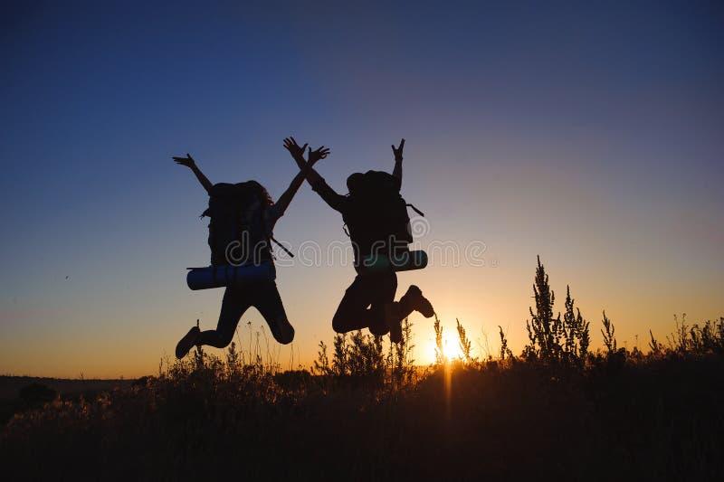 年轻夫妇剪影反对五颜六色的日落的 库存图片