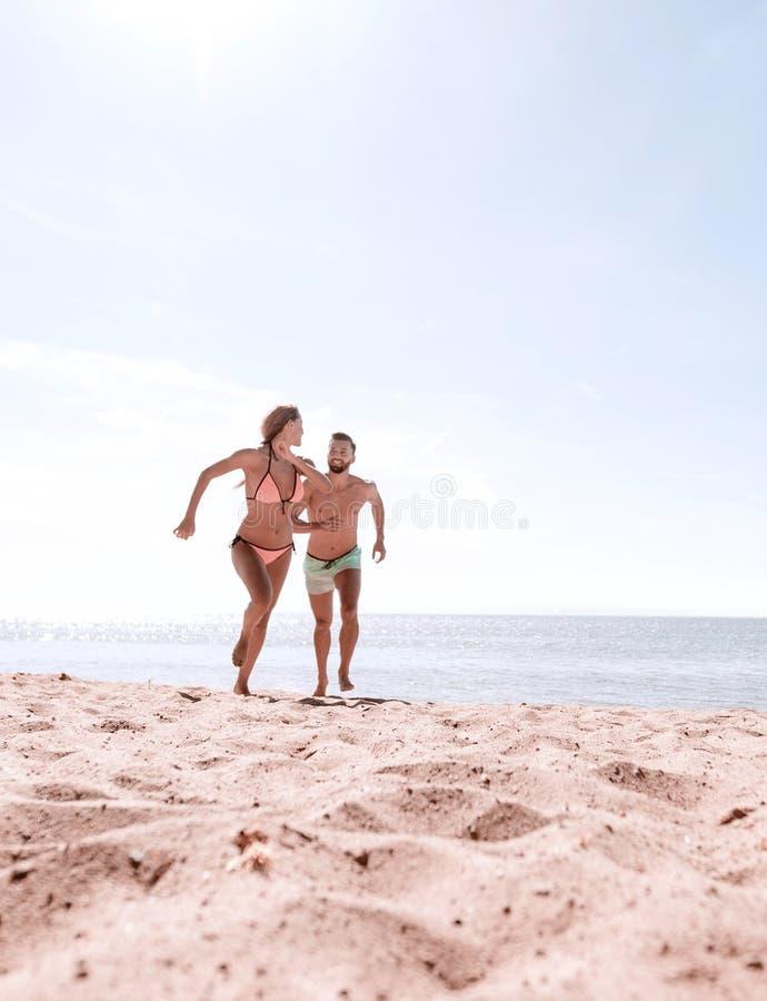年轻夫妇是花费时间的乐趣在海洋上 免版税库存照片