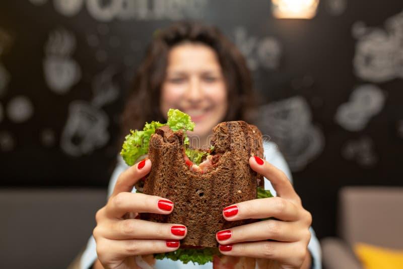 年轻女人举行被咬住的三明治特写镜头滑稽的被弄脏的protrait由她的两只手的 三明治在焦点 可能 库存图片