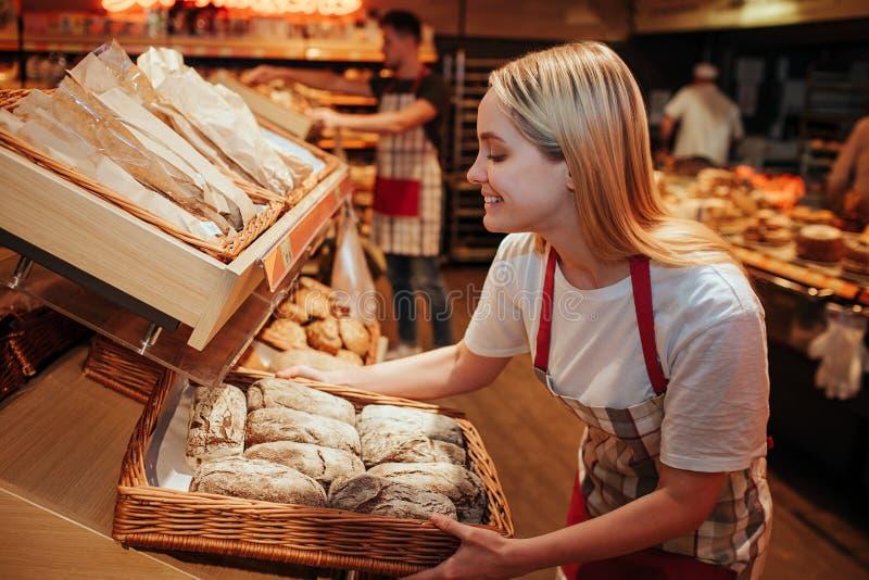 年轻女人举行bakset用新鲜面包在杂货店 她在架子和微笑投入了它 鲜美和delisious 工作 库存照片