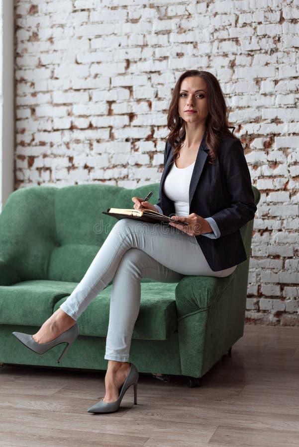 年轻女人企业教练的画象坐拿着笔记本的沙发架子看直接 库存图片