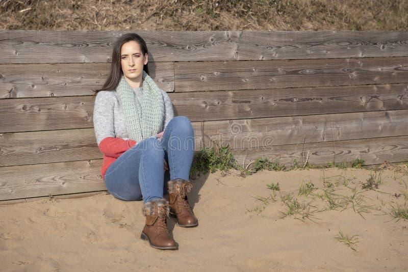 年轻女人坐的基于篱芭 图库摄影