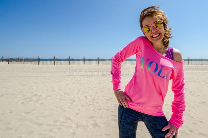年轻女人在海滩站立,穿有太阳镜的一件霓虹桃红色YOLO衬衣,作为她的在风的头发打击 库存照片