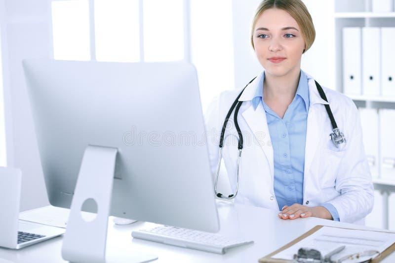 年轻女人医生在工作在看台式计算机显示器的医院 医师控制药物史纪录和 库存照片