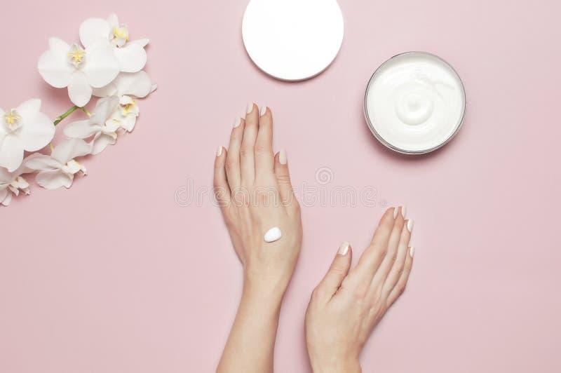 年轻女人润湿她的有化妆奶油色化妆水的手有奶油色身体乳白色的兰花植物的打开容器 库存照片