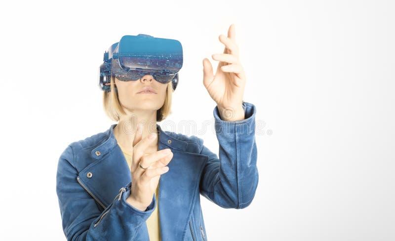 年轻女人戴虚拟现实眼镜并且接触在白色在VR经验期间隔绝的空气 库存照片