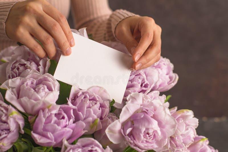 年轻女人手在双重紫罗兰色郁金香花上美丽的大花束把空白的贺卡放在黑暗的rustik背景的 免版税库存图片