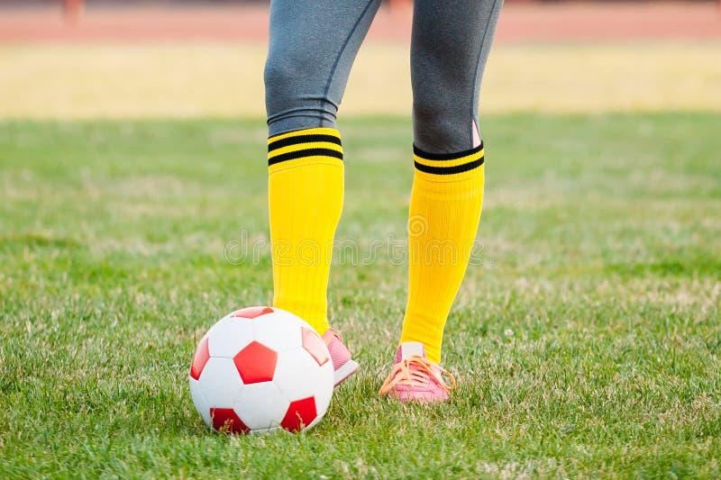 年轻女人足球运动员踢在橄榄球场的球 免版税图库摄影