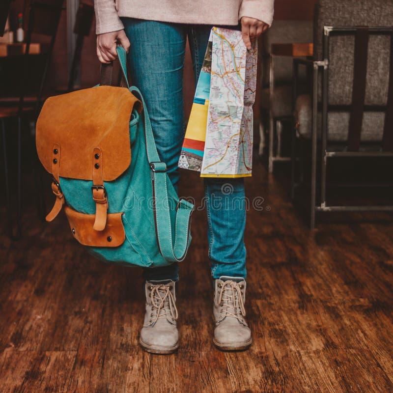年轻女人脚牛仔裤和起动的女孩旅客庄稼照片与户内背包和地图 库存图片