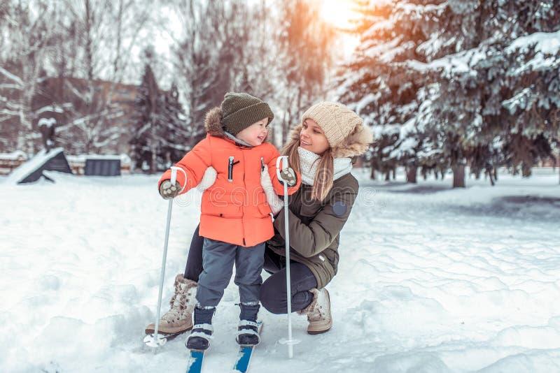 年轻女人,母亲在森林公园小心支持,小男孩儿子3-6岁,滑雪的冬天 第一体育 免版税图库摄影