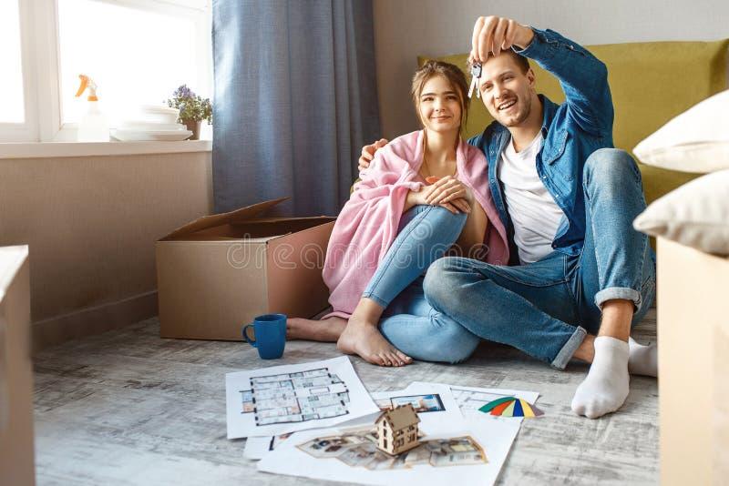 年轻家庭夫妇买了或租赁了他们的第一栋小公寓 愉快的人民坐地板和神色在人的钥匙 免版税库存照片