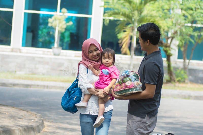 年轻回教家庭、运输、休闲、旅行和人概念-愉快的人,走的妇女和的女孩和带来果子 免版税库存图片