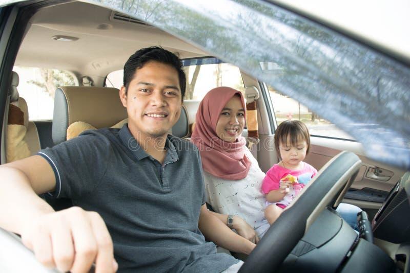年轻回教家庭、运输、休闲、旅行和人旅行在汽车looki的概念-愉快的人,妇女和女孩 免版税库存照片
