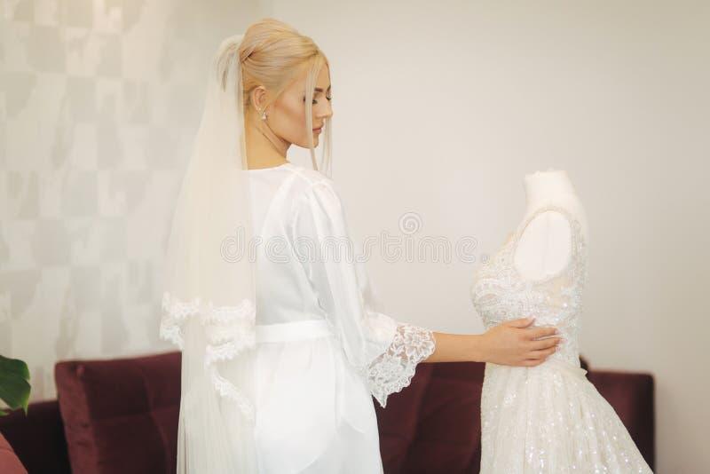 年轻和美丽的新娘在家 婚纱的金发女孩 库存图片