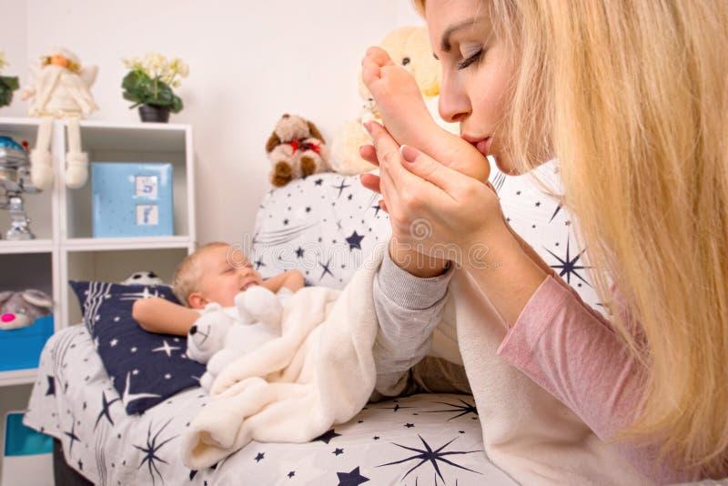 年轻母亲亲吻的婴孩脚 愉快的童年,爱家庭 图库摄影