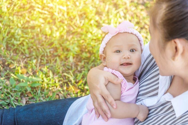 年轻母亲和小的5个月户外婴孩 一起使用在公园的秀丽母亲和她的孩子 室外画象愉快, 免版税库存图片