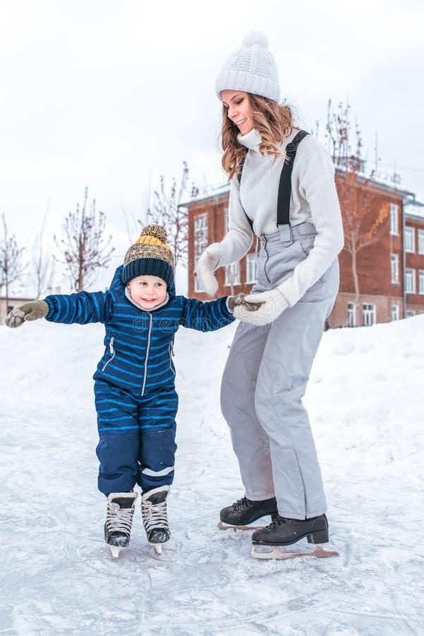 年轻母亲握儿子的手男孩的2-3年,滑冰的溜冰场冬天在城市公园 概念第一教训滑冰 免版税图库摄影