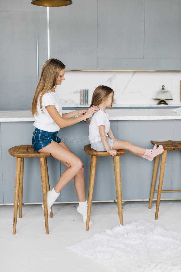 年轻母亲把她的小女儿的头发编成辫子 免版税库存图片