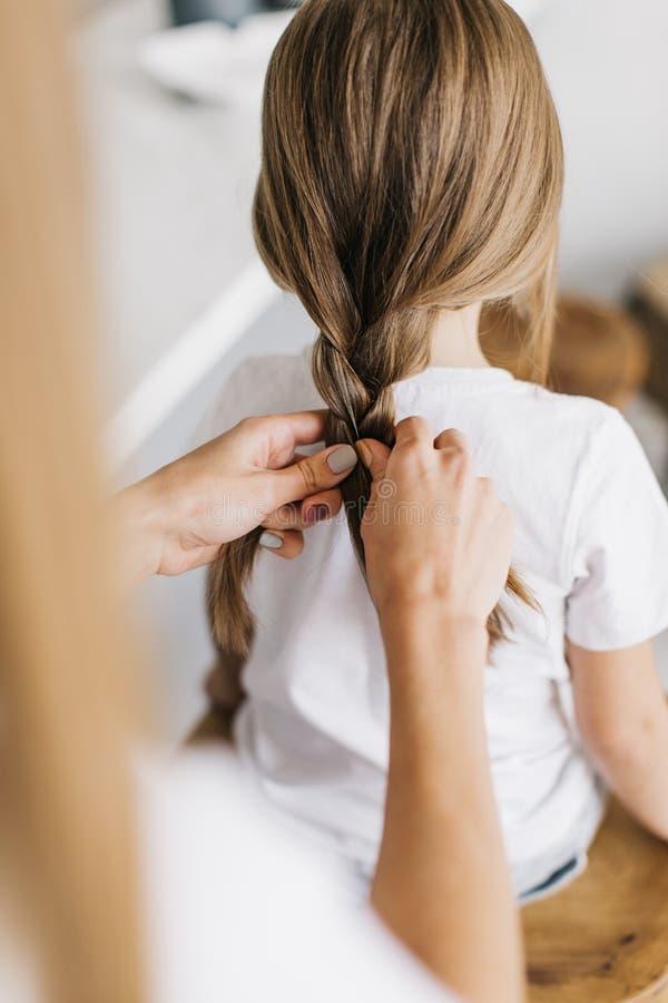 年轻母亲把她的小女儿的头发,特写镜头编成辫子 库存图片
