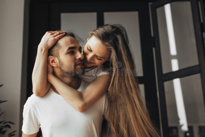 年轻浪漫夫妇是在家亲吻和享受公司彼此 图库摄影