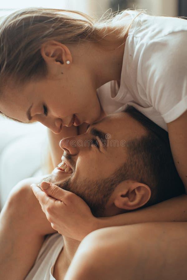 年轻浪漫夫妇特写镜头是在家亲吻和享受公司彼此 库存照片