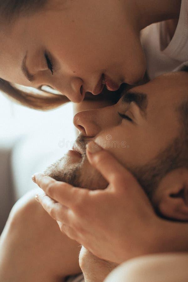 年轻浪漫夫妇特写镜头是在家亲吻和享受公司彼此 免版税图库摄影