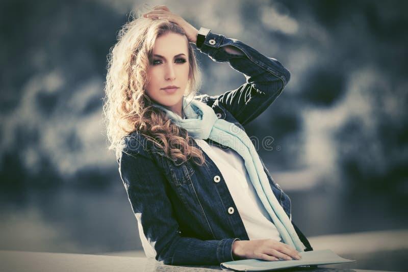 年轻深蓝牛仔布夹克走的时尚白肤金发的妇女室外 免版税库存图片
