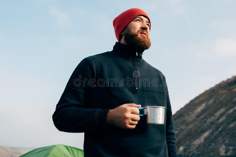 年轻探险家人饮用的茶或咖啡在山 有胡子的,拿着在手上一个杯子茶的佩带的红色帽子旅客人 免版税图库摄影