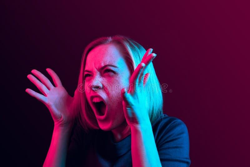 年轻情感恼怒的妇女尖叫在霓虹演播室背景 库存图片