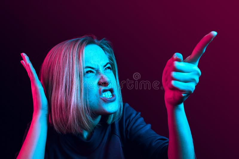 年轻情感恼怒的妇女尖叫在霓虹演播室背景 库存照片