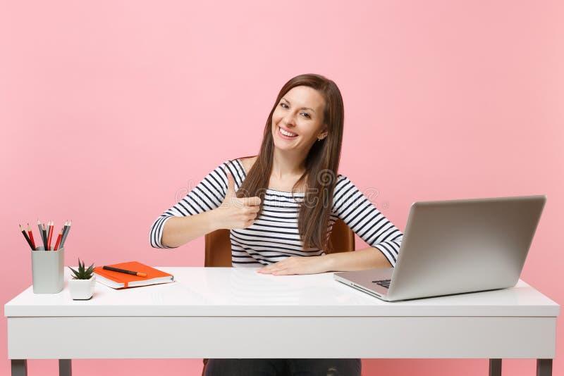 年轻成功的妇女陈列赞许坐并且运作在有在粉红彩笔隔绝的当代个人计算机膝上型计算机的白色书桌 免版税库存照片