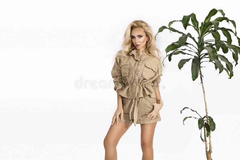 年轻时尚,时髦的微笑的白肤金发的妇女在演播室 时尚趋向服装,徒步旅行队样式,夏天成套装备,白色背景 库存图片