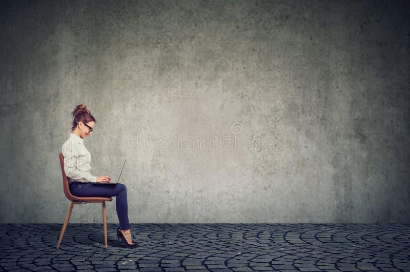年轻愉快的女商人坐椅子使用她的手提电脑 免版税库存照片