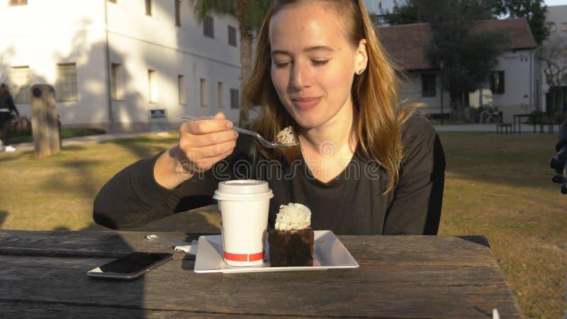 年轻愉快的妇女吃蛋糕室外在公园 免版税库存图片