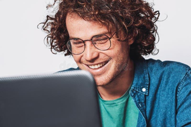 年轻愉快的商人特写镜头画象与卷发,佩带的圆的镜片的,研究他的膝上型计算机在办公室 免版税库存照片