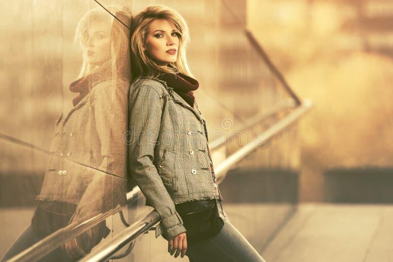 年轻穿在城市街道上的时尚白肤金发的妇女被检查的格子花呢披肩燃烧物 免版税库存照片