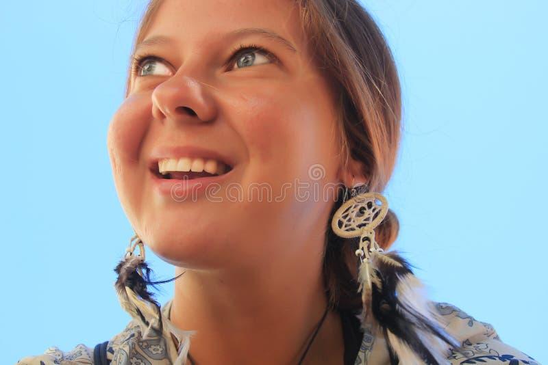 年轻红发女孩和耳环以梦想俘获器逗人喜爱的微笑的a的形式 图库摄影