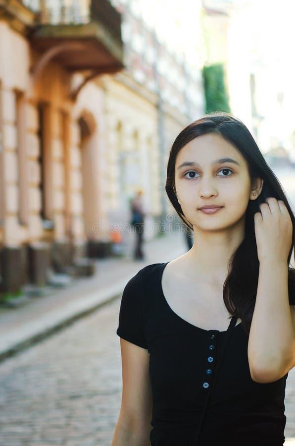 年轻美丽的俏丽的妇女画象有摆在城市的长发的 免版税库存图片