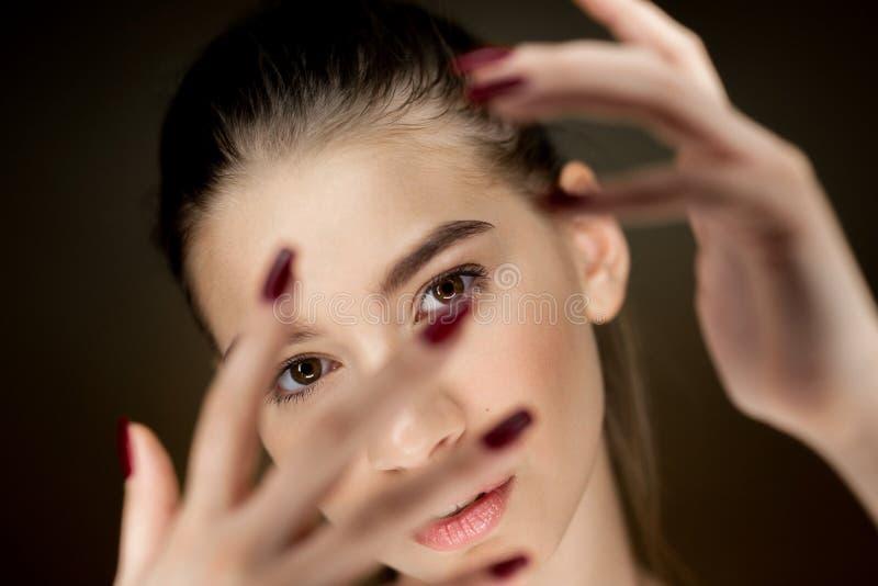 年轻美丽的棕色毛发的女孩画象有握她的在她的面孔前面的自然构成的手指 图库摄影
