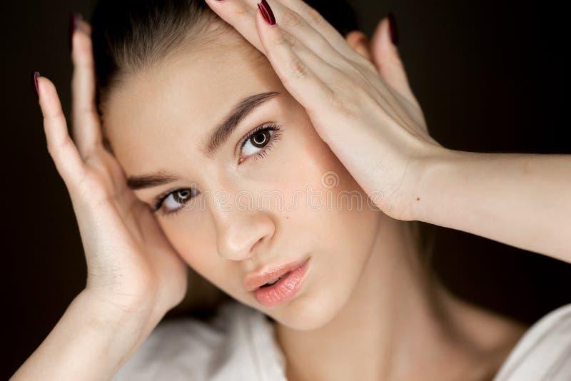 年轻美丽的棕色眼睛女孩画象有握她的在她的头的自然构成的手 库存照片