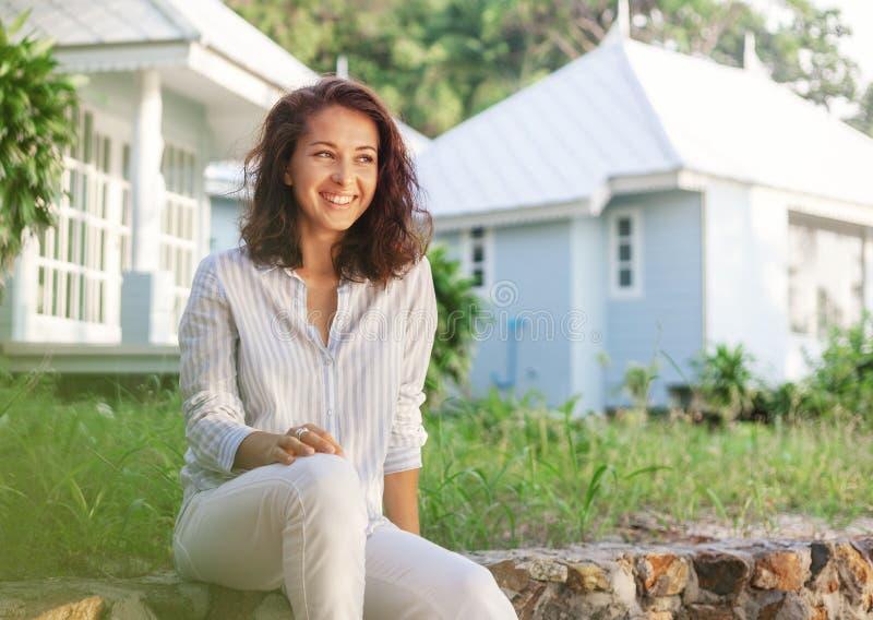 年轻美女在她的庭院里坐一美好的白色夏天好日子的背景 免版税库存图片