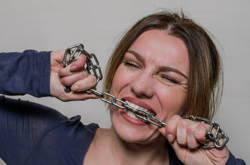年轻美女咬住与她的牙的链子,设法推测它  免版税库存照片