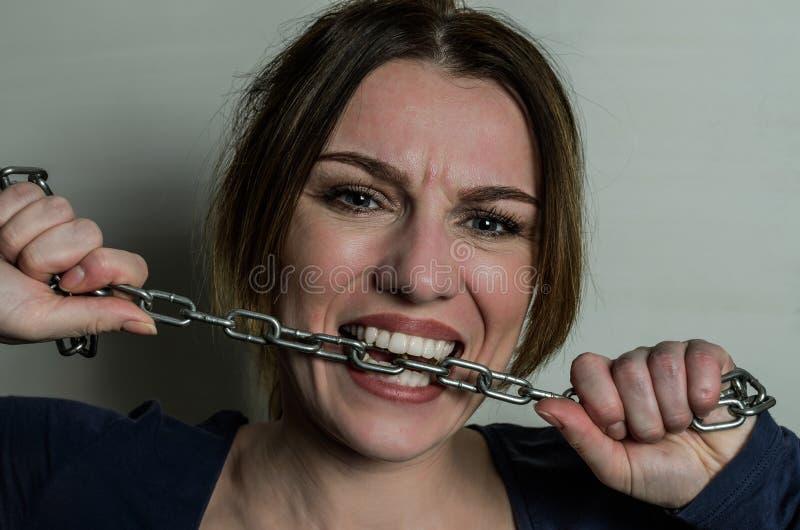 年轻美女咬住与她的牙的链子,设法推测它  库存图片