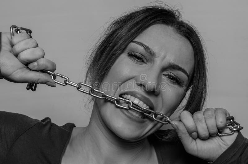 年轻美女咬住与她的牙的链子,设法推测它  库存照片