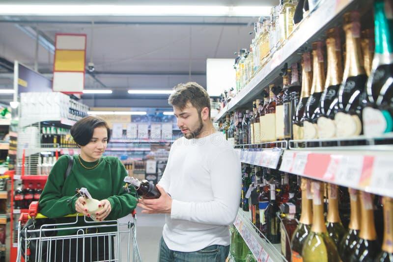 年轻美好的夫妇在商店买酒精 夫妇在超级市场选择酒 库存照片