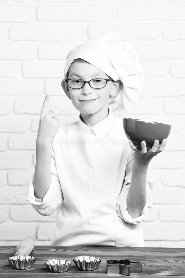 年轻白色制服和帽子的男孩小逗人喜爱的厨师厨师在与站立与滚针的玻璃的滑稽的面孔近的桌 免版税库存图片