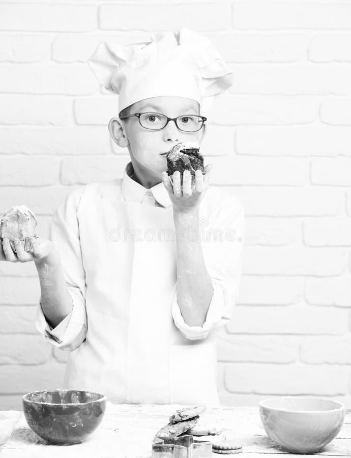 年轻白色制服和帽子的男孩逗人喜爱的厨师厨师在与站立与五颜六色的玻璃的被弄脏的面孔面粉近的桌 免版税库存照片